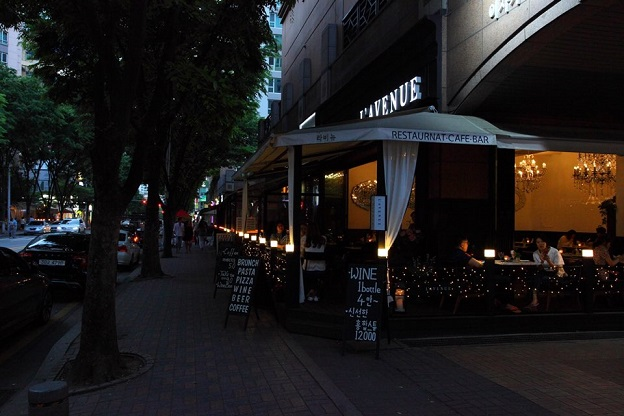 People enjoying a meal or coffees at L`AVENUE cafe, one of the cafes in the Café Street in Jeongja-dong.