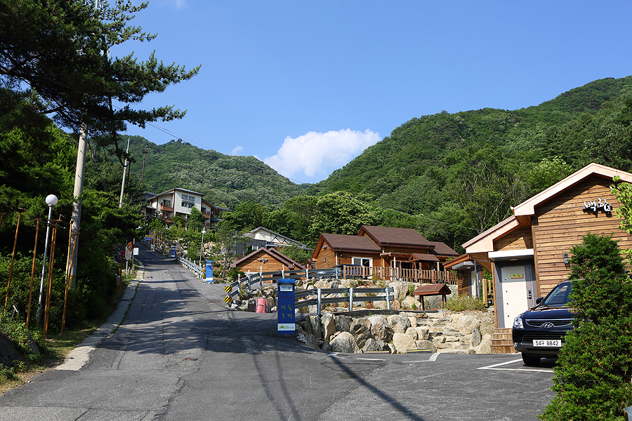 As Chungnyeongsan Recreational Forest is located in the middle of Chungnyeongsan Mountain, pensions are set along the uphill road to the mountain with a greenish mountain and clear sky in the backgound.