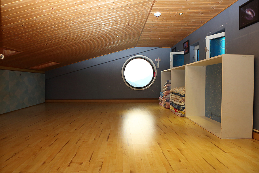 A picture of the clean attic room with small round and sqaure windows.