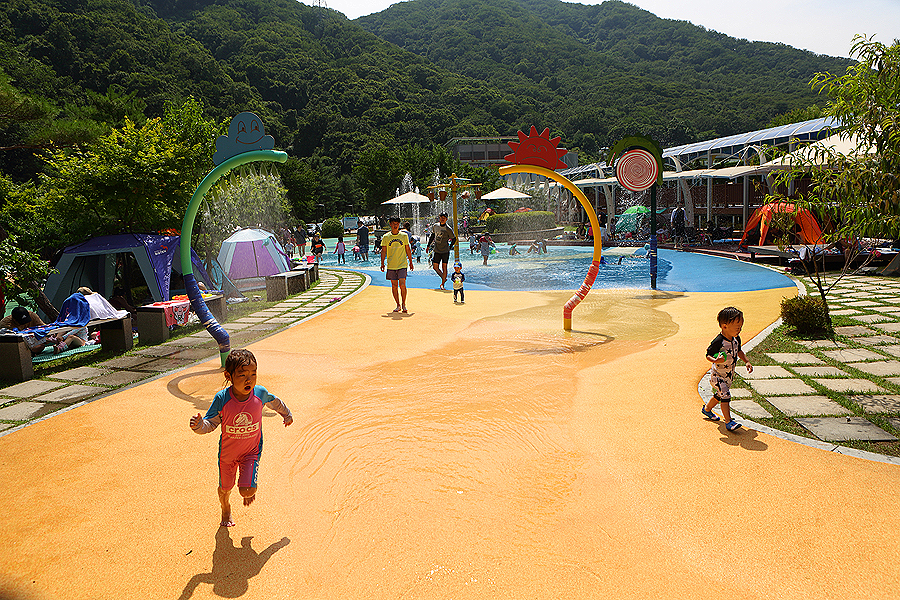 There are many families with kids playing at the water park of shallow water. And  a blue and green mountain to the background. visitors sets up their tants on either side of the water park as well.